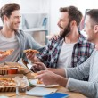 Young men eating pizza  in office — Stock Photo #73022253