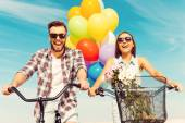 Couple riding on bicycles with colorful balloons — Стоковое фото