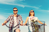 Young couple smiling and riding on bicycles — Stock Photo
