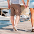 Couple holding hands while walking along quay — Stock Photo #74088785