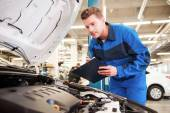 Man in uniform examining car in workshop — Stock Photo