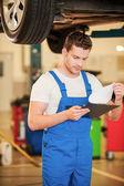 Man in uniform holding clipboard in workshop — Stock Photo