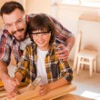 Carpenter teaching son to work with wood — Stock Photo #74125025