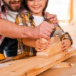 Carpenter teaching son to work with wood — Stock Photo #74124971