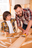 Carpenter showing his son how to sand wood — Stock Photo