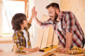Carpenter and son giving high-five — Stockfoto