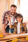 Carpenter embracing his son — Stock Photo