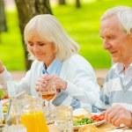 Senior couple praying before family dinner — Stock Photo #74728899