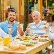 Young and senior couples sitting at the dining table — Stock Photo #74729081