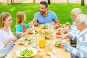 Happy family enjoying meal outdoors — Stock Photo