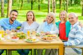 Family sitting at the dining table outdoors — Stock Photo