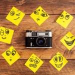 Retro camera surrounding by adhesive notes — Stock Photo #74859081