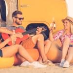 花很大的时间与朋友。快乐的年轻人玩吉他,而两位年轻女子坐在他身旁,喝啤酒的黄色面包车在背景中 — 图库照片 #75407535