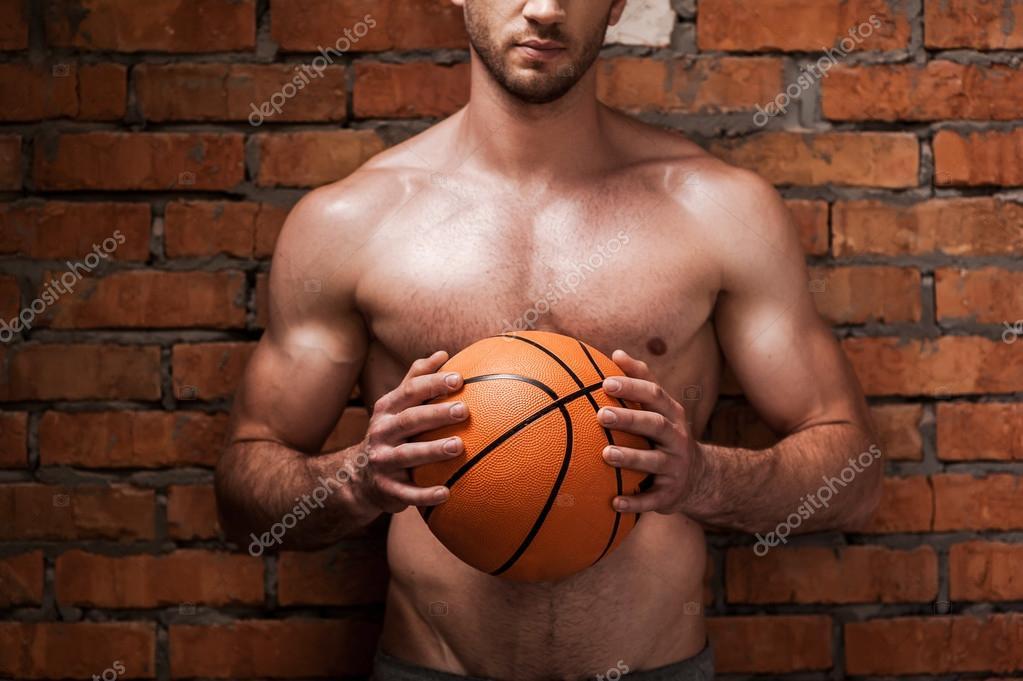 肌肉发达的男人抱着篮球球