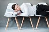 Man keeping eyes closed while laying on chairs — Stock Photo