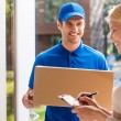 Delivery man holding and woman putting signature — Stock Photo #76029291