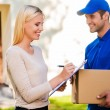 Delivery man and woman putting signature in clipboard — Stock Photo #76029303