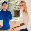 Woman holding cardboard box with delivery man — Stock Photo #76029407