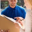 Just sign here. Handsome young delivery man holding a cardboard box while beautiful young woman putting signature in clipboard — Stock Photo #76029417