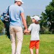 Man and his son walking on  golf course — Stock Photo #76697683