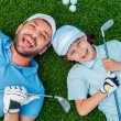 Little boy and his father holding golf clubs — Stock Photo #76698337