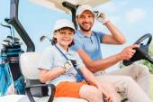 Man and his little son sitting in golf cart — Stock Photo