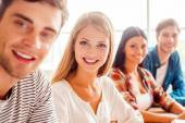 Young people sitting in row in classroom — Stock Photo