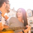 Woman smiling while her boyfriend playing guitar — Stock Photo #80685890