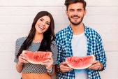 Loving couple holding slices of watermelon — Stock Photo