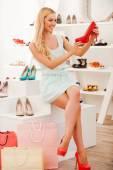 Женщина держит красное обуви в магазине — Стоковое фото