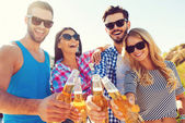 Young people stretching out bottles with beer — Stock Photo