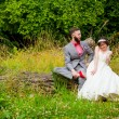 Bride and Groom Sitting Portrait Outdoors — Stock Photo #56509213