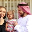 Portrait of a young couple in Arab robes with a small child in her arms. Arab family in the background of the city. Happy Arab family smiling at the camera. Young parents with a child. — Vídeo de stock #51953261