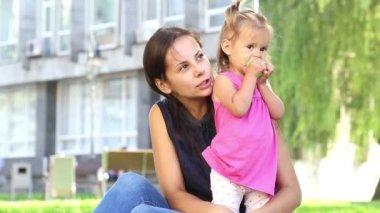 Joven madre con bebé en una ciudad park.mother jugando con el bebé en el parque en el grass.family en el parque en vacation.mom con una chica en la naturaleza. — Vídeo de Stock