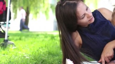 Young mother with baby in a city park.Mother playing with baby in the park on the grass.Family in the park on vacation.Mom with a little girl in nature. — Stock Video