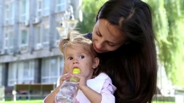 Young beautiful mother feeds the child in the park.Young mother with baby lunch on the grass.Mom feeds the little girl in the park.The child in the park next to my mom eats a banana. — Wideo stockowe