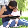 Mother teaches a little girl.Mom teaches a child to play on the tablet.Young mother with baby in the park playing on the laptop. — Stockvideo #53036577