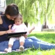 Mother teaches a little girl.Mom teaches a child to play on the tablet.Young mother with baby in the park playing on the laptop. — Стоковое видео #53036687