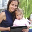Mother teaches a little girl.Mom teaches a child to play on the tablet.Young mother with baby in the park playing on the laptop. — Stockvideo #53037241