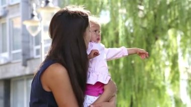 Portrait of a young mother with baby on hands at the park. Young mother with baby in a city park.Mother playing with baby in the park on the grass.Mom with a little girl in nature. — Wideo stockowe