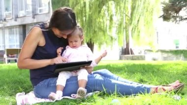 Mother teaches a little girl.Mom teaches a child to play on the tablet.Young mother with baby in the park playing on the laptop. — Stockvideo