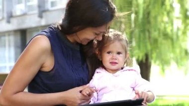 Mother teaches a little girl.Mom teaches a child to play on the tablet.Young mother with baby in the park playing on the laptop. — Wideo stockowe