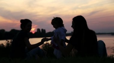 Girlfriend with baby on sunset.Silhouette of three girls with a child.Three mothers with baby on nature.Young mother with baby at the lake at sunset. — Stock Video