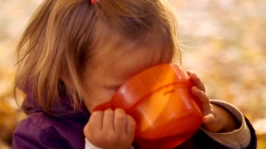 Child drinks tea in autumn park.A small child is drinking tea in nature.Little girl drinks tea with emotionally mugs.Autumn picnic. Emotions child closeup. — Stock Video
