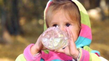 L'enfant boit l'eau minérale. Petite fille est l'eau potable dans la nature. Petite fille dans des vêtements lumineux est l'eau potable provenant d'une bouteille dans le parc en automne. Émotions enfant agrandi. — Vidéo