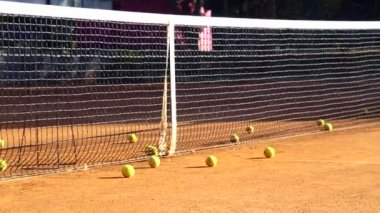 Tennis court before the game.Balls on the tennis court.Balls roll down to cover a tennis court. — Stockvideo
