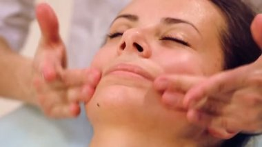Facial massage beautiful girl.Portrait of a girl in a massage parlor.Beautician doing massage of female faces.Massage face girl close-up. — Video Stock
