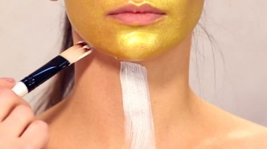 Applying cosmetic mask on face of beautiful girl.Use of face masks in cosmetology.Applying cosmetic golden mask on the face.Decorative cosmetics.Portrait of the girl close up in a beauty salon. — Stock Video