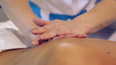 Massage procedure in spa salon.Massage of female back in the masseur.Masseur massaging the back of the girl.Closeup hands of the masseur. — Stock Video