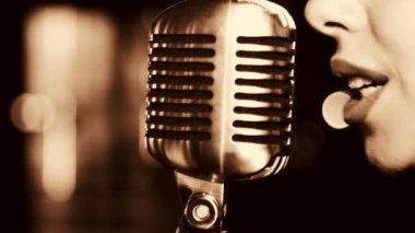 Belle jeune femme chantant. La jeune chanteuse chante dans le micro. Portrait de gros plan de la chanteuse, rétro, noir et blanc. — Vidéo